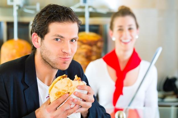 Döner kebab - vriendelijke verkoper en klant in een turks fastfoodrestaurant, met een vers gemaakt pitabroodje of kebab voor een spies