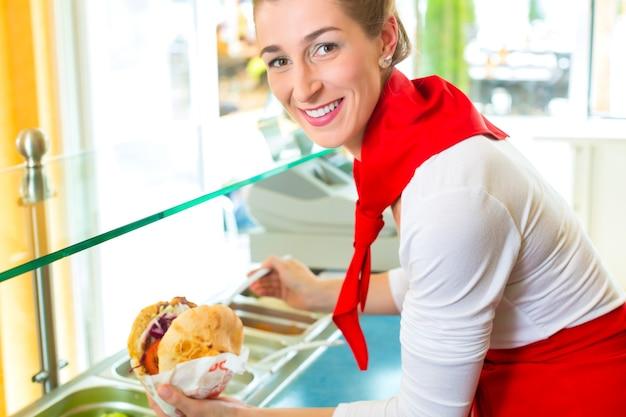 Döner kebab - vriendelijke verkoper in een turks fastfoodrestaurant, met een vers gemaakt pitabroodje of kebab