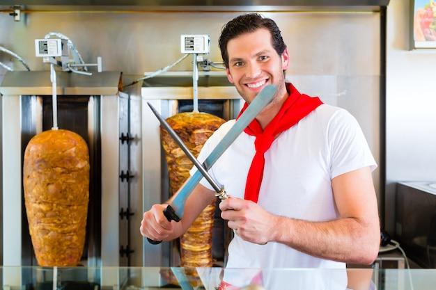 Döner kebab - vriendelijke verkoper in een turks fastfoodrestaurant, vlees snijden met een scherp mes voor een spies