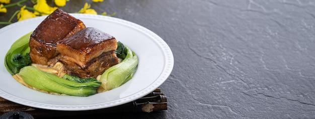 Dong po rou (dongpo varkensvlees) in een mooi bord met groene groente