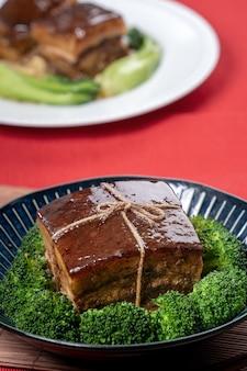 Dong po rou dongpo varkensvlees in een mooie blauwe plaat met groene broccoli plantaardige traditionele feestelijke gerechten voor chinees nieuwjaar keuken maaltijd close-up