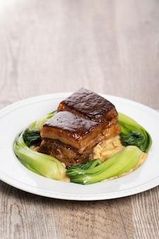 Dong po rou (dongpo-varkensvlees) in een mooie blauwe plaat met groene broccoligroente, traditioneel feestelijk voedsel.