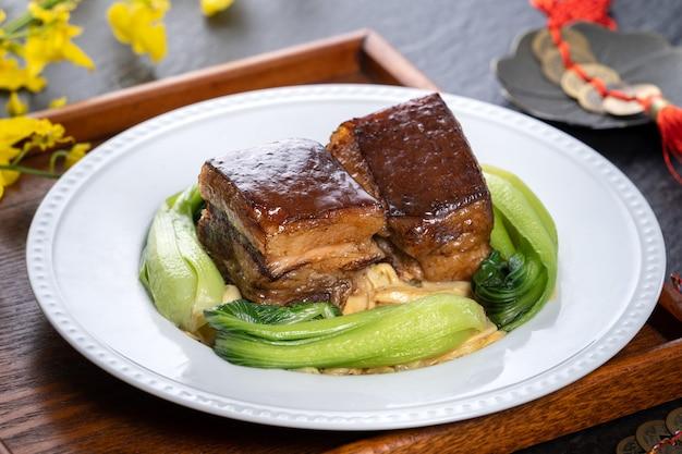 Dong po rou (dongpo-varkensvlees) in een mooie plaat met groene groente, traditioneel feestelijk voedsel