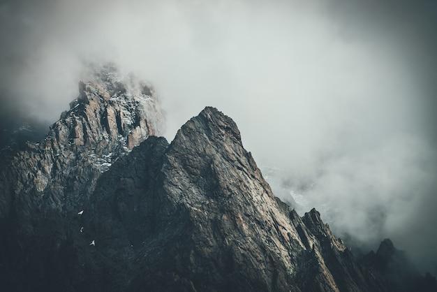 Donker atmosferisch surrealistisch landschap met donkere rotsachtige bergtop in lage wolken in grijze bewolkte hemel. grijze lage wolk op hoge top. hoge zwarte rots met sneeuw in lage wolken. surrealistische sombere bergen.