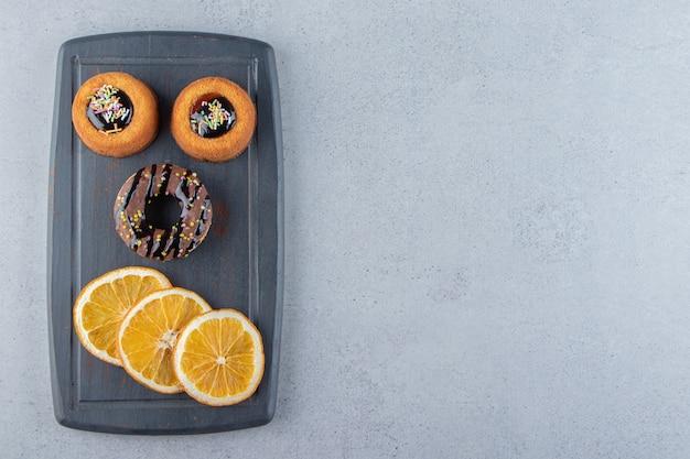 Donker bord met smakelijke chocoladedonuts en geleicakes