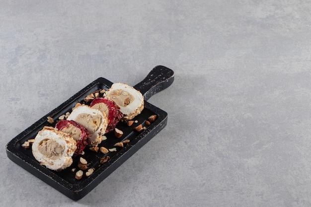 Donker bord van heerlijke gesneden turkse lokums en kopje thee stenen achtergrond.