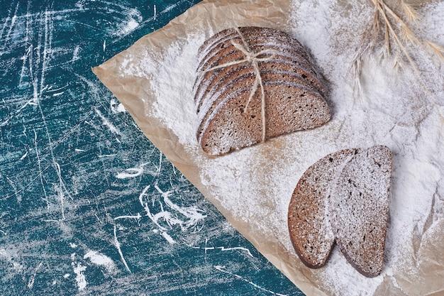 Donker brood gebonden met rustieke draad op blauwe tafel.