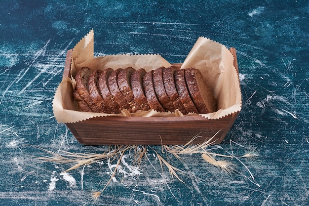 Donker brood in een houten dienblad op blauw.
