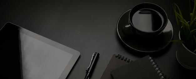 Donker bureau met digitale tablet, briefpapier, pen, koffiekopje en kopie ruimte