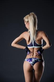 Donker contrastbeeld van de rug en billen van de geschiktheidsvrouw. ze traint op zwarte achtergrond in de studio.