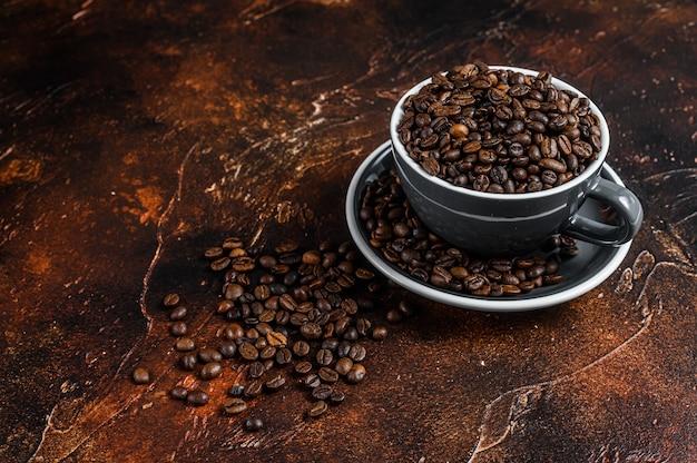 Donker gebrande koffiebonen in een kopje.