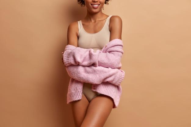 Donker gevild vrouwelijk model omarmt zichzelf heeft een mooi sexy lichaam draagt ondergoed en een trui met lange mouwen geeft om zichzelf.