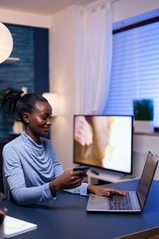 Donker gevilde vrouw die online transactie maakt met behulp van een plastic creditcard die aan het bureau in het kantoor aan huis zit. werknemer die een betalingstransactie uitvoert vanuit huis op digitale notebook.