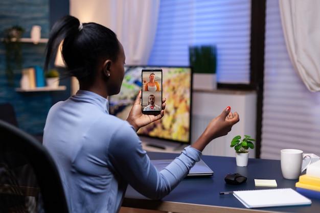 Donker gevilde vrouw die 's avonds laat smartphone gebruikt in een kantoor aan huis die met mensen in videoconferentie bespreekt. drukke werknemer met behulp van moderne technologie netwerk draadloos overuren maken voor werk.