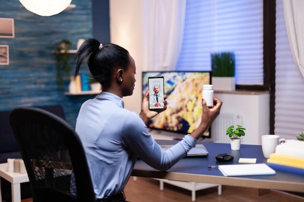 Donker gevilde vrouw luisteren arts praten over behandeling tijdens online conferentie. zwarte patiënt in een videogesprek met dokter die gezondheidsproblemen van de vrouw bespreekt.