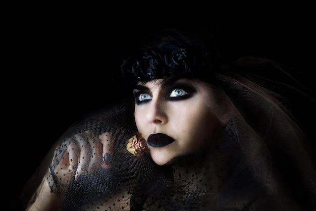 Donker haar gotische vrouw met zwarte lippen make-up en droge roos in haar hand