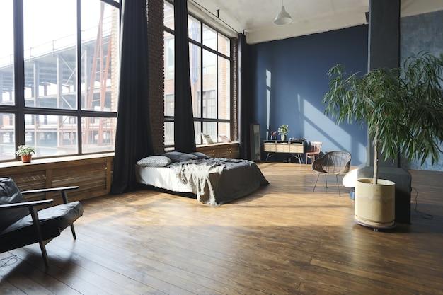 Donker interieur van een modern, stijlvol enorm open studio-appartement in loftstijl met kolommen en hoge plafonds.