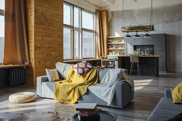 Donker loft-stijl interieur van groot gezellig landhuis. open appartement met keuken, rustzone en slaapgedeelte. enorme ramen en houten decoratie