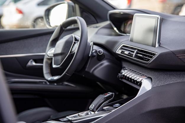 Donker luxe auto-interieur. zwart lederen multifunctioneel stuur, start- en stopmotor, dashboard, stuur en bestuurdersstoel