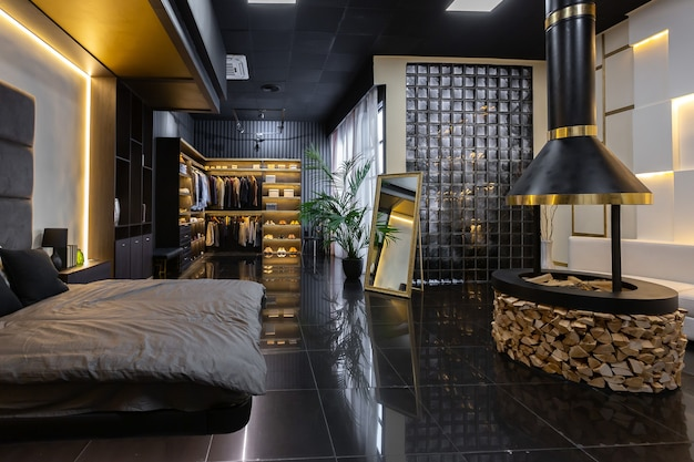 Donker modern stijlvol mannelijk appartement interieur met verlichting, decoratieve muren, open haard, kleedruimte en groot raam