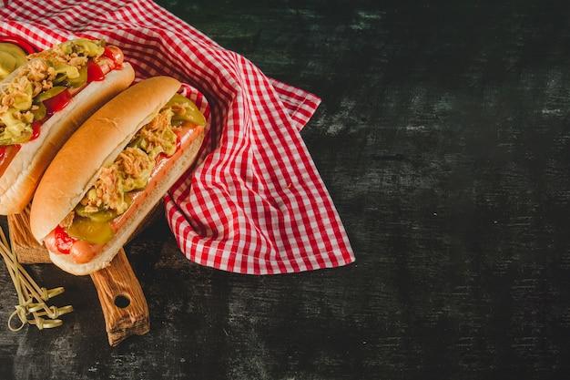 Donker oppervlak met tafelkleed en twee heerlijke hotdogs