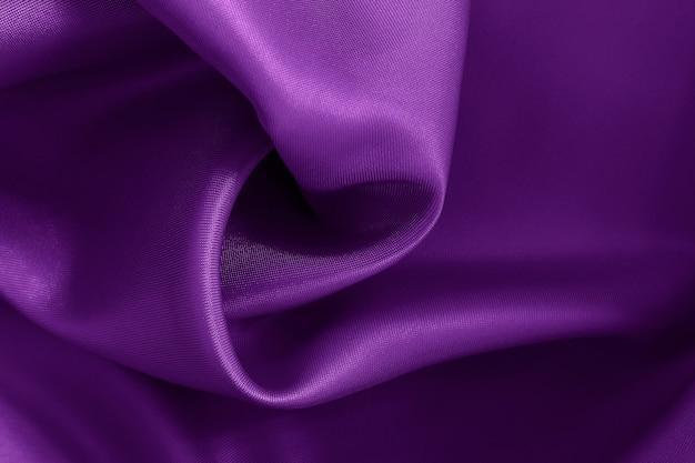 Donker paarse stof textuur achtergrond, verfrommeld patroon van zijde of linnen.