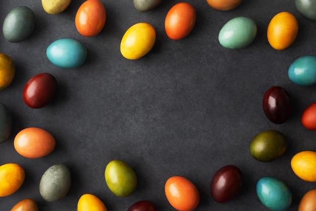 Donker paaskader met eieren gekleurd met natuurlijke kleurstof - uienschil, kurkuma, rode kool, koffie, carcade.