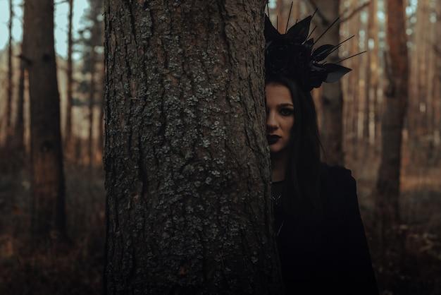 Donker portret van een heksenmeisje in een zwart kostuum in het bos