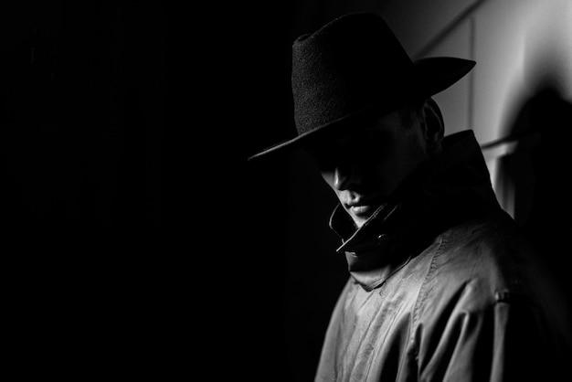 Donker portret van een man in een regenjas met een hoed 's nachts op straat in een misdaad noir-stijl