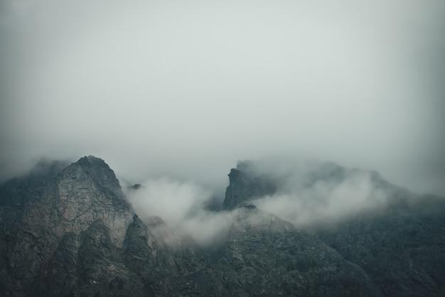 Donker sfeervol berglandschap met scherpe rotsen in lage bewolking. donkere rotsen in grijs bewolkt weer. somber berglandschap met grijze lage wolken op ruwe rotsen. minimalisme met rocky mountains.