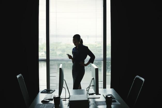 Donker silhouet die van vrouw zich tegen venster in bureau bevinden en smartphone gebruiken