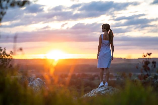 Donker silhouet van een jonge vrouw die op een steen staat en in de zomer buiten geniet van het uitzicht op de zonsondergang.