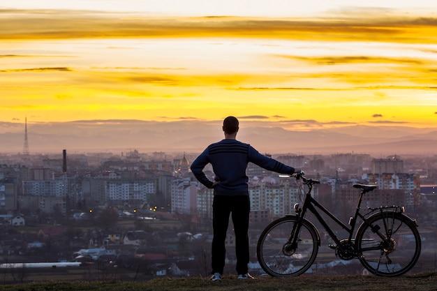 Donker silhouet van een man die in de buurt van een fiets met uitzicht op de nachtstad