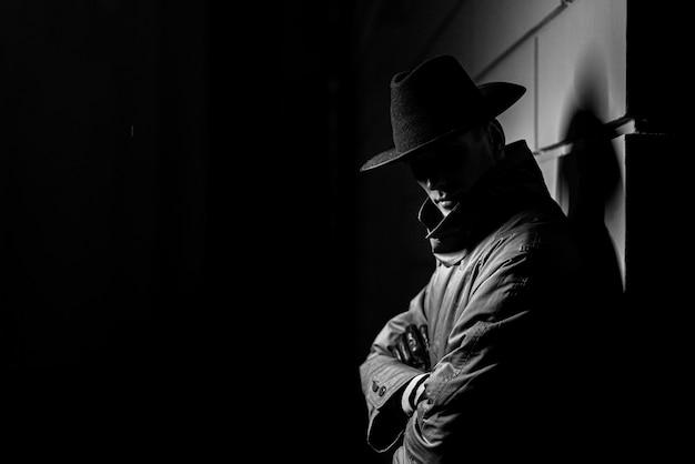 Donker silhouet van een man in een regenjas met een hoed 's nachts op straat