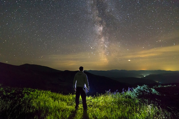 Donker silhouet van een mens die zich in bergen bij nacht bevindt die van melkachtige maniermening geniet.