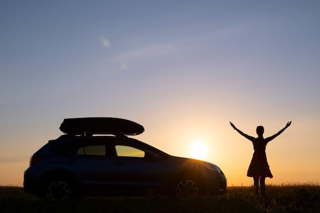 Donker silhouet van een vrouwelijke chauffeur die in de buurt van haar auto op een grasveld staat en geniet van het uitzicht op de heldere zonsondergang. jonge vrouw ontspannen tijdens road trip naast suv-voertuig.