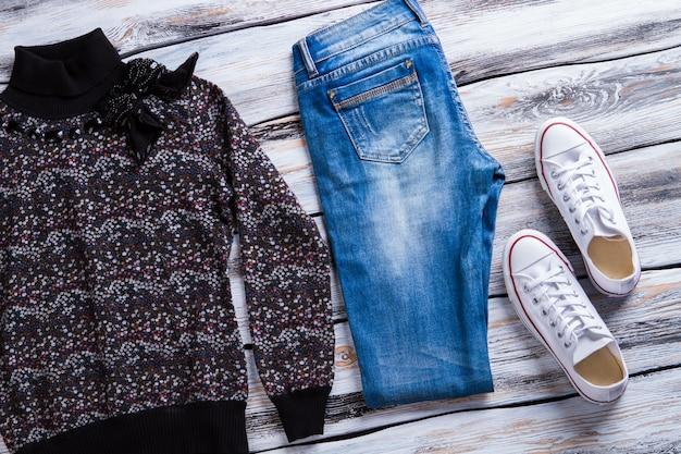 Donker sweatshirt en spijkerbroek. damestrui met strikapplicatie. casual herfstkleding te koop. selectie van eenvoudige kleding.