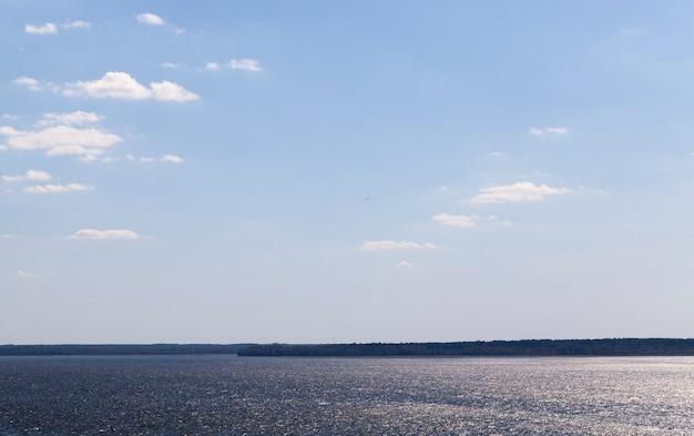 Donker water in een groot meer, zomerlandschap met een blauwe lucht