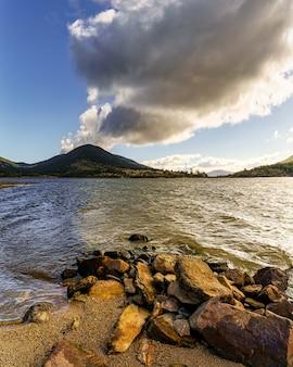 Donker winterlandschap met zoetwatermeer, bergen aan de horizon en donkere wolken aan de hemel. lozoya-reservoir, madrid. spanje.