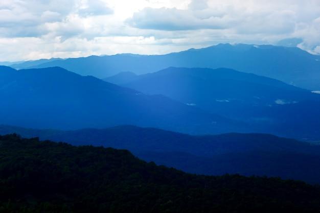 Donkerblauw mysterieus berglandschap in bewolkte avondrood