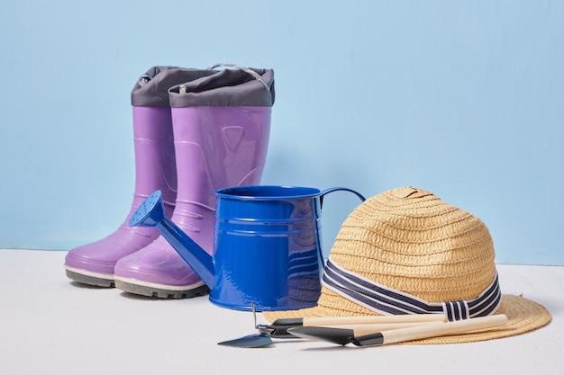 Donkerblauwe gieter kleine schoppen strooien hoed en baby rubberen laarzen op een houten tafel