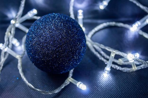 Donkerblauwe glanzende kerstbal met kerstverlichting