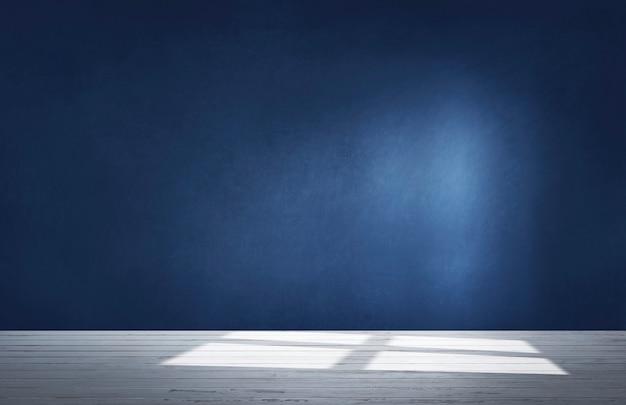 Donkerblauwe muur in een lege ruimte met een concrete vloer