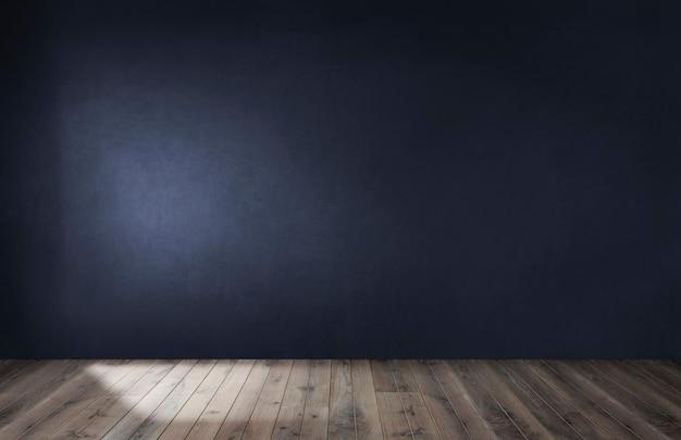 Donkerblauwe muur in een lege ruimte met een houten vloer