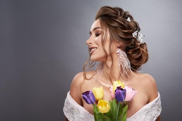 Donkerbruin bruidprofiel met bloemrijk kapsel en kleurrijke bloemen