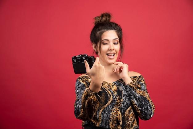 Donkerbruin fotomeisje dat haar foto's op glimlachende manier neemt.