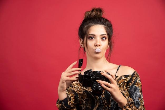 Donkerbruin fotomeisje dat kauwgom kauwt en fotogeschiedenis controleert.