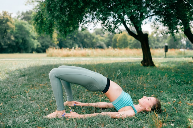Donkerbruin geschiktheidsmeisje dat yoga doet openlucht