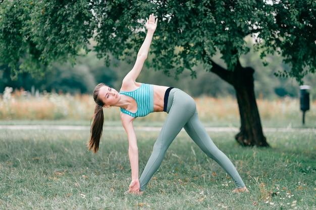 Donkerbruin geschiktheidsmeisje dat yoga in de zomerpark doet.