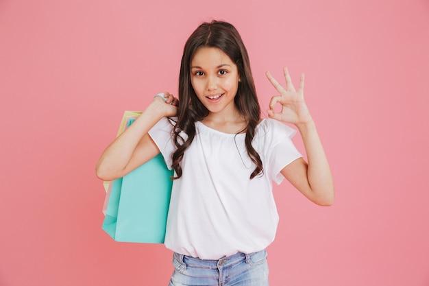 Donkerbruin kaukasisch meisje 8-10 in vrijetijdskleding die bij camera glimlachen en ok teken tonen terwijl kleurrijke boodschappentassen met aankopen, die over roze achtergrond worden geïsoleerd